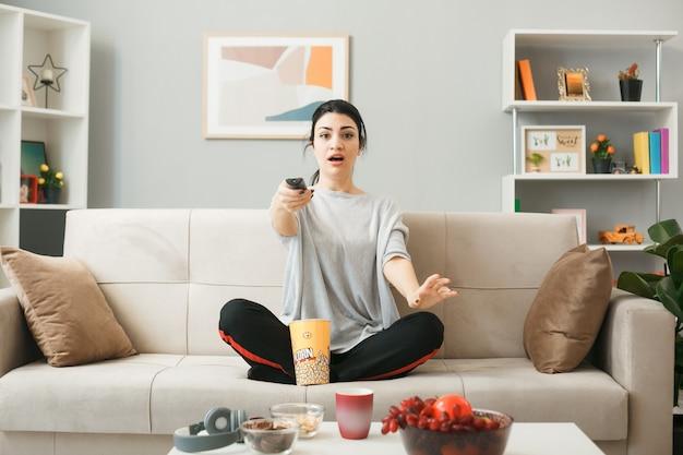 Ragazza sorpresa con il secchio del popcorn che tiene il telecomando della tv, seduta sul divano dietro il tavolino da caffè nel soggiorno