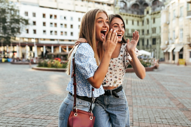 Surprised young girlfriends look away and cover mouths with hands