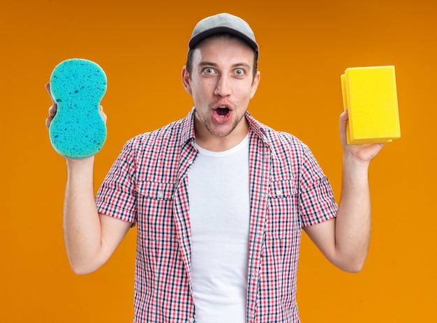 Sorpreso giovane ragazzo pulitore che indossa il cappuccio tenendo le spugne per la pulizia isolate su sfondo arancione
