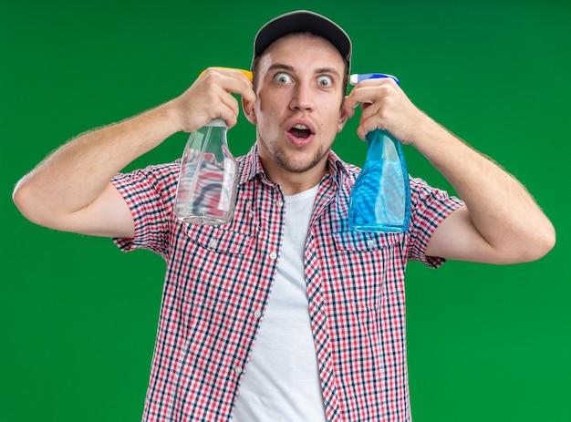 녹색 벽에 고립 된 청소 에이전트와 자살 제스처를 보여주는 모자를 쓰고 놀란 젊은 남자 청소기