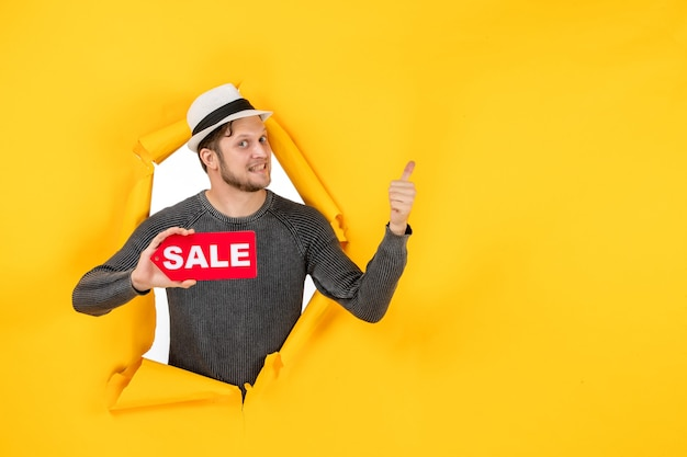 Surprised young guy holding sale sign and pointing back in a torn on yellow wall