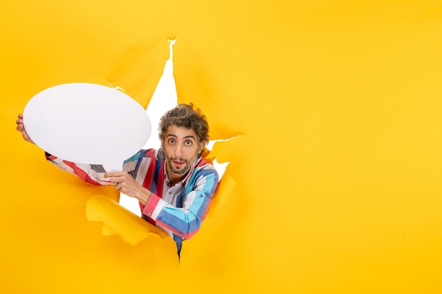 Surprised young guy holding white balloon and posing for camera in a torn hole and free background in yellow paper