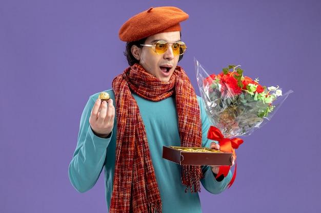Удивленный молодой парень в день святого валентина в шляпе с шарфом и очками держит и смотрит на букет с коробкой конфет, изолированной на синем фоне