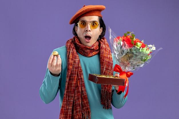 Удивленный молодой парень на день святого валентина в шляпе с шарфом и очками, держа букет с коробкой конфет, изолированной на синем фоне
