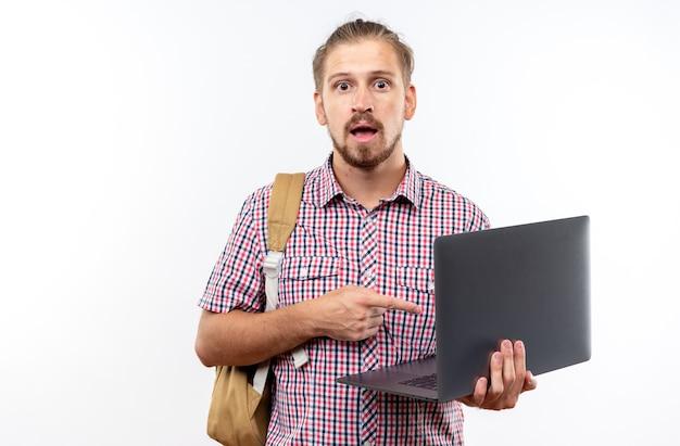 Sorpreso giovane studente che indossa lo zaino che tiene e punta al computer portatile isolato sul muro bianco