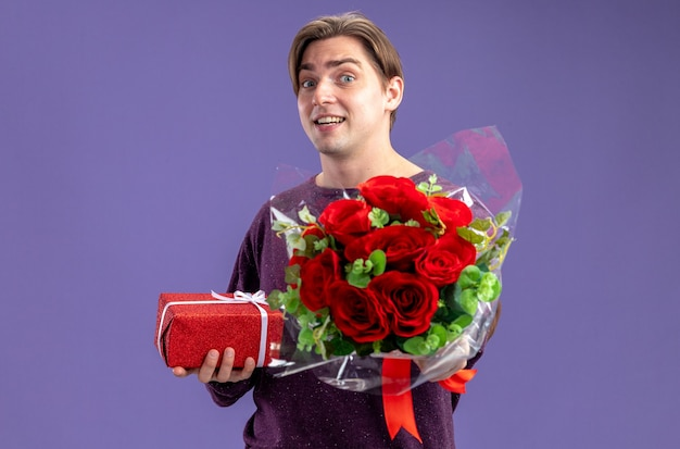 Surprised young guy on valentines day holding gift box with bouquet isolated on blue background
