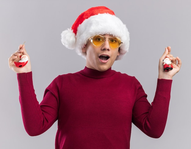 Surprised young guy wearing christmas hat holding christmas toys isolated on white wall