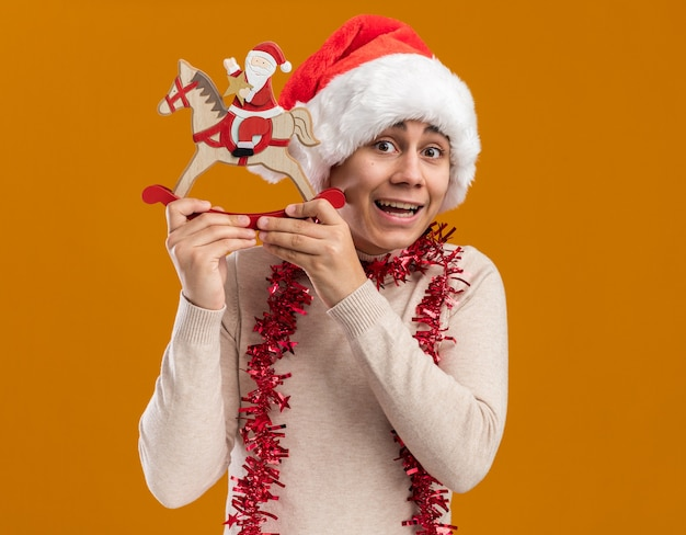 Surprised young guy wearing christmas hat with garland on neck holding christmas toy isolated on yellow wall