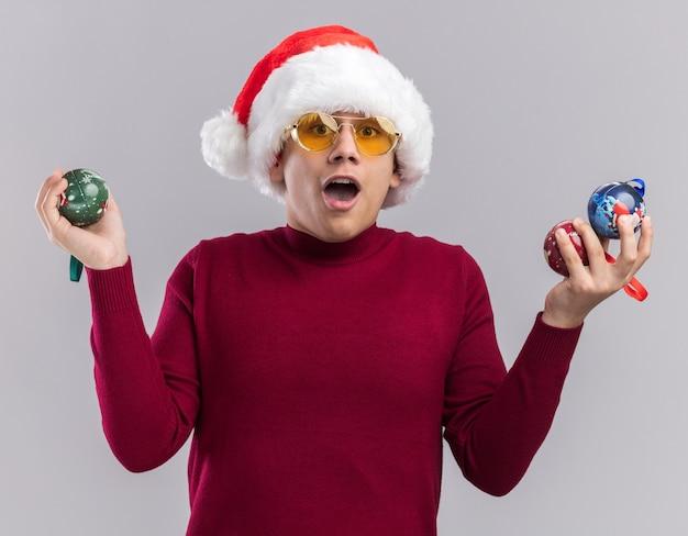 흰색 배경에 고립 된 크리스마스 트리 볼을 들고 안경 크리스마스 모자를 쓰고 놀란 된 젊은 남자