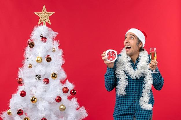 サンタクロースの帽子をかぶって、クリスマスツリーの近くに立っているワインと時計のグラスを持って驚いた若い男