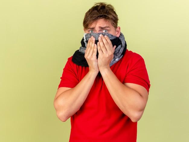 Удивленный молодой красивый блондин больной мужчина в шарфе, закрывающем рот, держа руки во рту, изолированном на оливково-зеленой стене с копией пространства