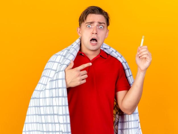 オレンジ色の壁に隔離された温度計を保持し、指している格子縞に包まれた驚いた若いハンサムな金髪の病気の男