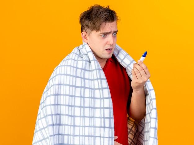 Giovane uomo malato biondo bello sorpreso avvolto in holding plaid e guardando termometro isolato su sfondo arancione