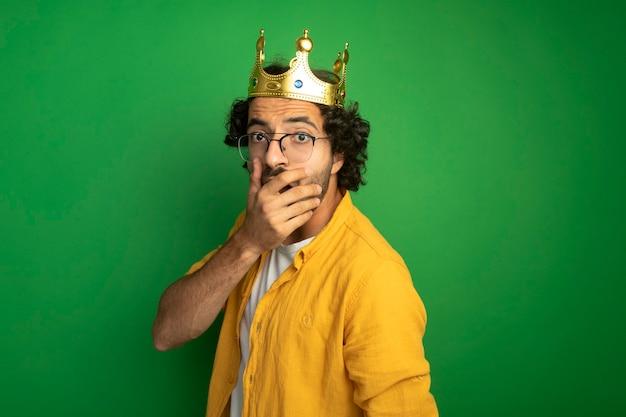 眼鏡と王冠を身に着けている驚いた若いハンサムな白人男性がコピースペースで緑の背景に分離された口に手を置いてカメラを見て縦断ビューで立っ