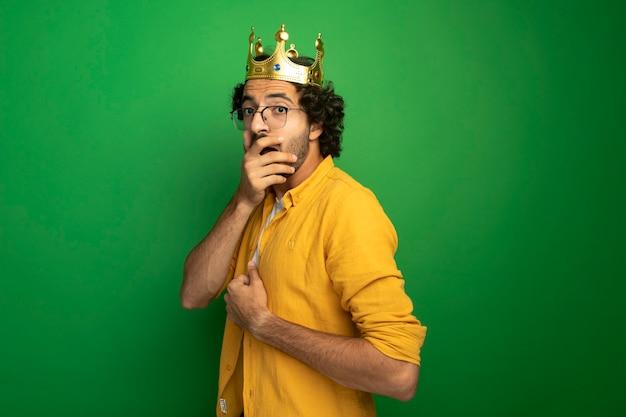 Giovane uomo caucasico bello sorpreso con gli occhiali e la corona in piedi nella vista di profilo che guarda l'obbiettivo che tiene la mano sulla bocca isolata su fondo verde con lo spazio della copia