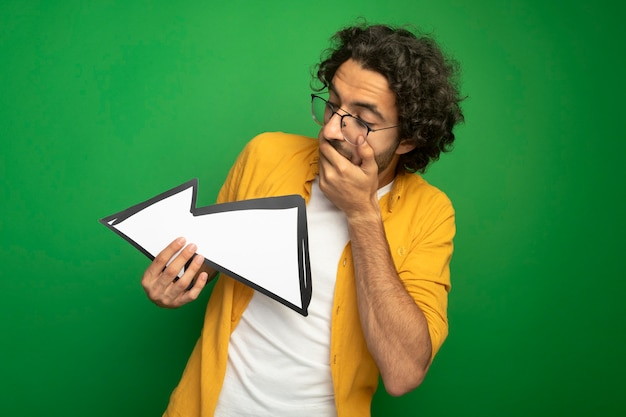 Удивленный молодой красивый кавказский мужчина в очках, держащий стрелку, указывающую в сторону, смотрящую на нее, держа руку на рте, изолированном на зеленом фоне с копией пространства