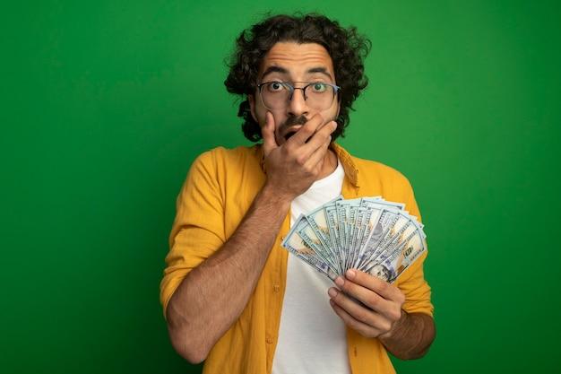 Giovane uomo caucasico bello sorpreso con gli occhiali che tengono soldi tenendo la mano sulla bocca isolata sulla parete verde con lo spazio della copia