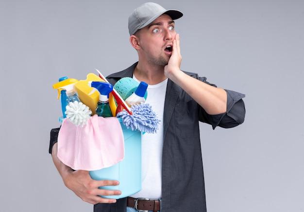 白い壁に隔離された頬に手を置くクリーニングツールのバケツを保持しているtシャツとキャップを身に着けている驚いた若いハンサムなクリーニング男
