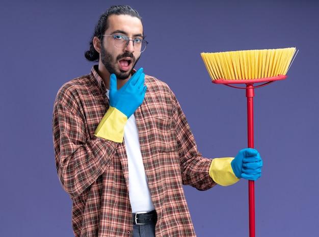 青い壁に隔離されたあごに手を置くモップを保持しているtシャツと手袋を身に着けている驚いた若いハンサムな掃除人