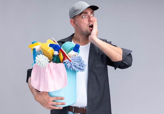 Surprised young handsome cleaning guy wearing t-shirt and cap holding bucket of cleaning tools putting hand on cheek isolated on white wall