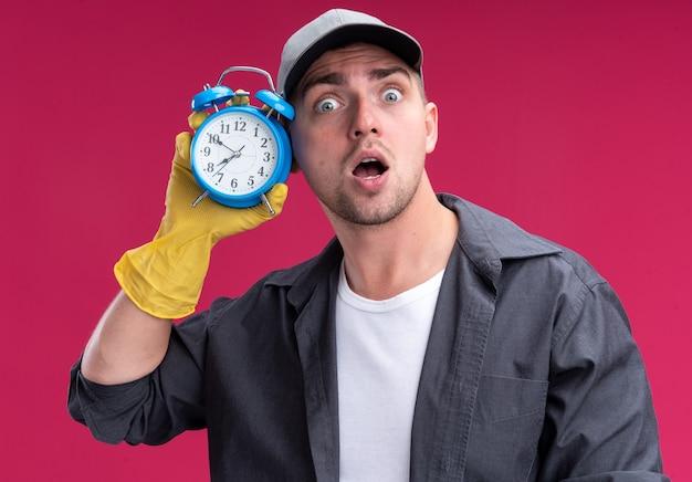 Giovane ragazzo bello delle pulizie sorpreso che indossa t-shirt e berretto con i guanti che tengono e ascolta la sveglia isolata sulla parete rosa