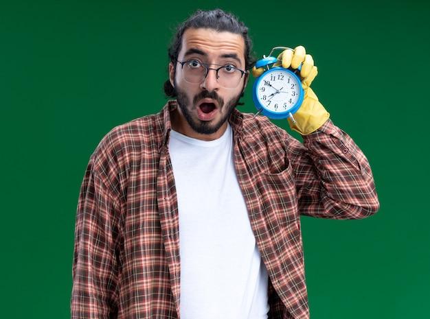 Giovane ragazzo bello delle pulizie sorpreso che indossa t-shirt e guanti che tengono e ascolta la sveglia isolata sulla parete verde