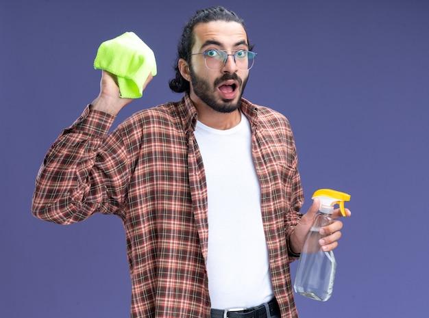 Giovane ragazzo bello delle pulizie sorpreso che indossa la t-shirt che tiene il flacone spray con uno straccio isolato sulla parete blu