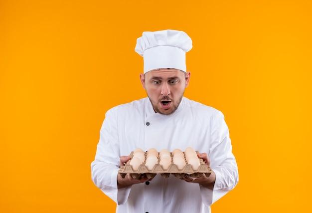 Giovane cuoco bello sorpreso nella tenuta dell'uniforme del cuoco unico e che esamina il cartone delle uova isolato sullo spazio arancio