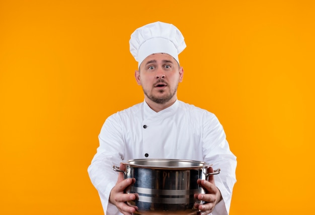 Surprised young handsome cook in chef uniform stretching out boiler  on isolated orange space