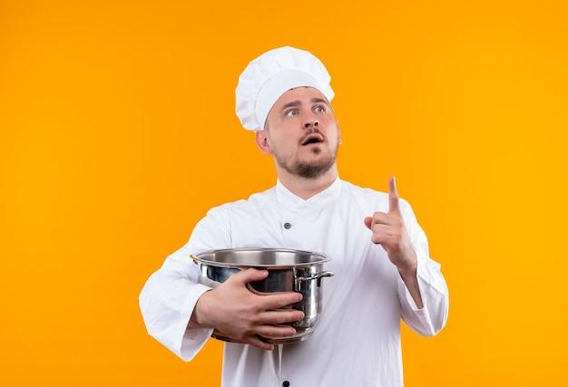 ボイラーを保持し、孤立したオレンジ色のスペースで右側を見て指を上げるシェフの制服を着た若いハンサムな料理人を驚かせた