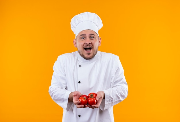 オレンジ色のスペースで隔離のトマトを保持しているシェフの制服を着た若いハンサムな料理人を驚かせた