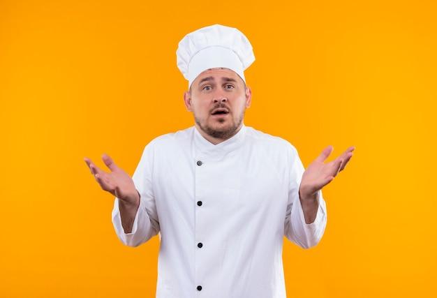 孤立したオレンジ色のスペースに空の手を示すシェフの制服を着た驚いた若いハンサムな料理人