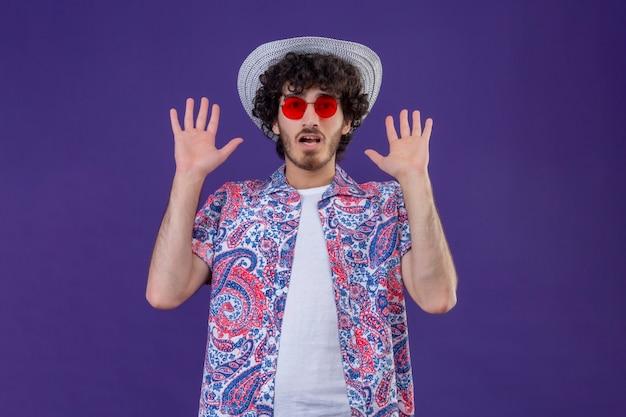 복사 공간이 격리 된 보라색 벽에 빈 손을 보여주는 선글라스와 모자를 쓰고 놀란 젊은 잘 생긴 곱슬 여행자 남자