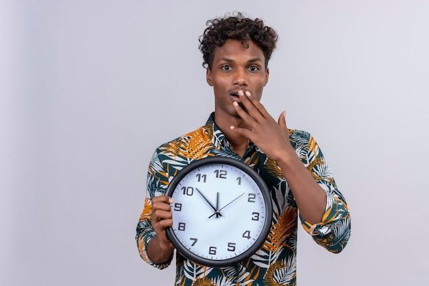 白い背景の壁時計を押しながら手で口を覆っている巻き毛の驚いた若いハンサムな浅黒い男
