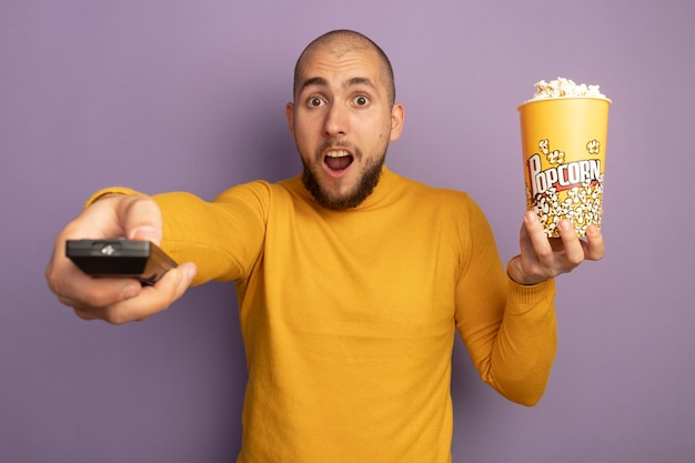 Удивленный молодой красивый парень, держащий ведро попкорна и протягивающий пульт от телевизора, изолированный на фиолетовой стене
