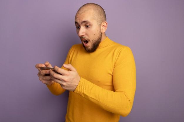 Giovane ragazzo bello sorpreso che tiene e che esamina telefono isolato sulla porpora
