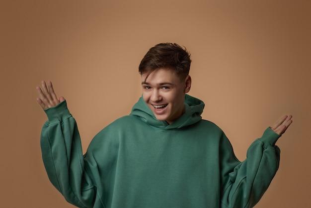 緑のスウェットシャツで驚いた若いハンサムな男
