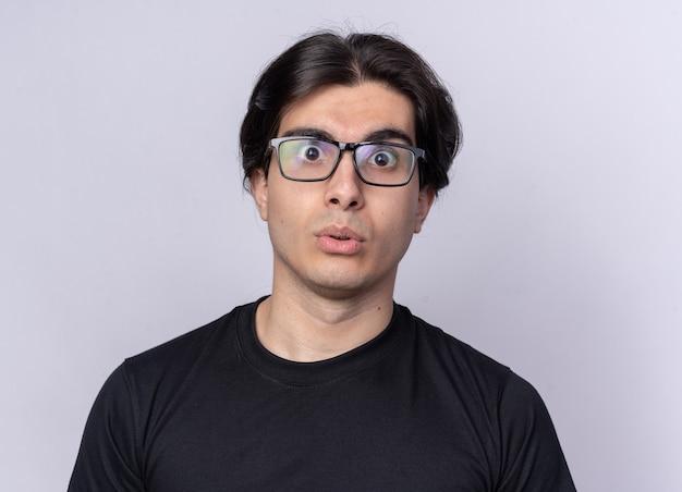 검은 티셔츠와 흰 벽에 고립 된 안경을 쓰고 놀란 젊은 잘 생긴 남자