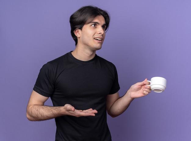 黒のtシャツを持って、紫色の壁に隔離されたコーヒーのカップを手で指して驚いた若いハンサムな男