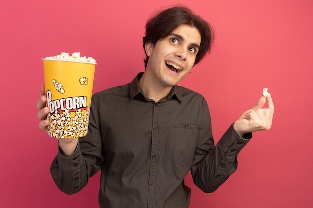 분홍색 벽에 고립 된 팝콘 평화와 팝콘의 양동이를 들고 검은 티셔츠를 입고 놀란 젊은 잘 생긴 남자