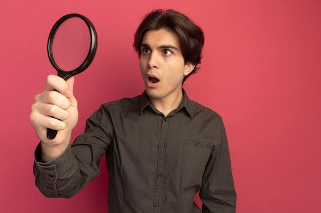 Giovane ragazzo bello sorpreso che indossa la maglietta nera che tiene e che guarda la lente d'ingrandimento isolata sulla parete rosa