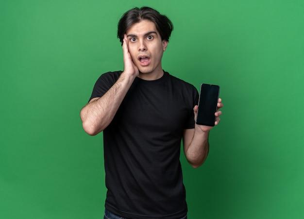 전화를 들고 녹색 벽에 고립 된 뺨에 손을 넣어 검은 티셔츠를 입고 놀란 젊은 잘 생긴 남자