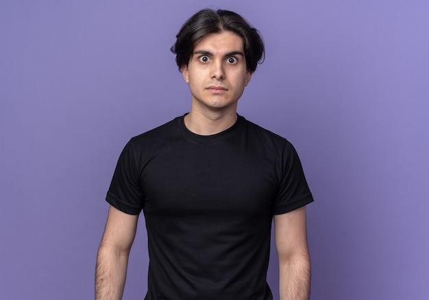 보라색 벽에 고립 된 검은 티셔츠를 입고 놀란 젊은 잘 생긴 남자