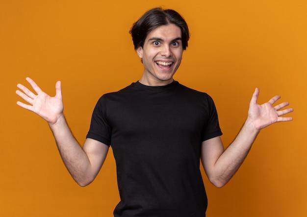 오렌지 벽에 고립 된 손을 확산 검은 티셔츠를 입고 놀란 젊은 잘 생긴 남자