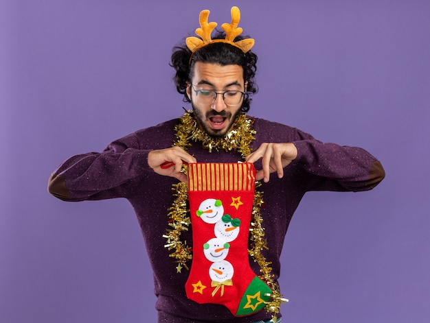 Surprised young handsome guy wearing christmas hair hoop with garland on neck holding and looking at into christmas socks isolated on blue background