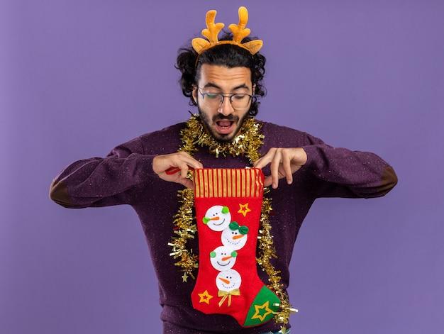 Удивленный молодой красивый парень в рождественском обруче для волос с гирляндой на шее держит и смотрит в рождественские носки, изолированные на синем фоне
