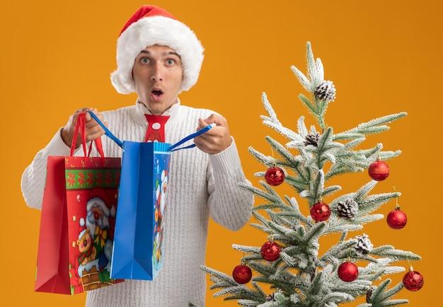 Sorpreso giovane bel ragazzo che indossa cappello di natale e cravatta di babbo natale in piedi vicino a un albero di natale decorato che tiene sacchetti regalo di natale aprendone uno che sembra isolato sul muro arancione
