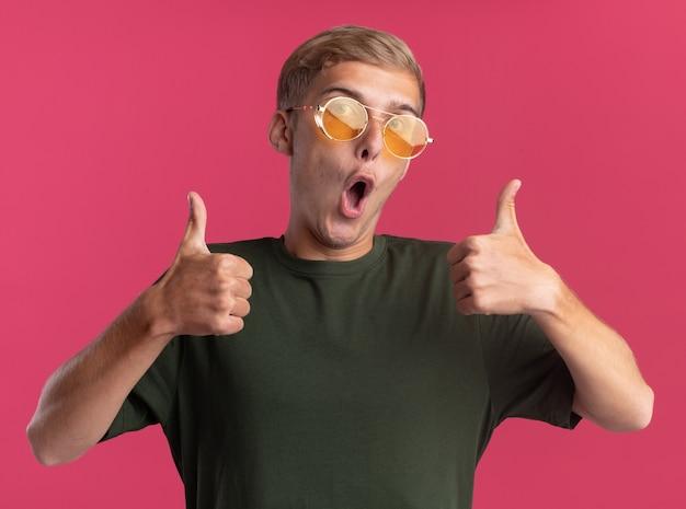 녹색 셔츠와 엄지 손가락을 보여주는 안경을 쓰고 놀란 젊은 잘 생긴 남자는 분홍색 벽에 고립