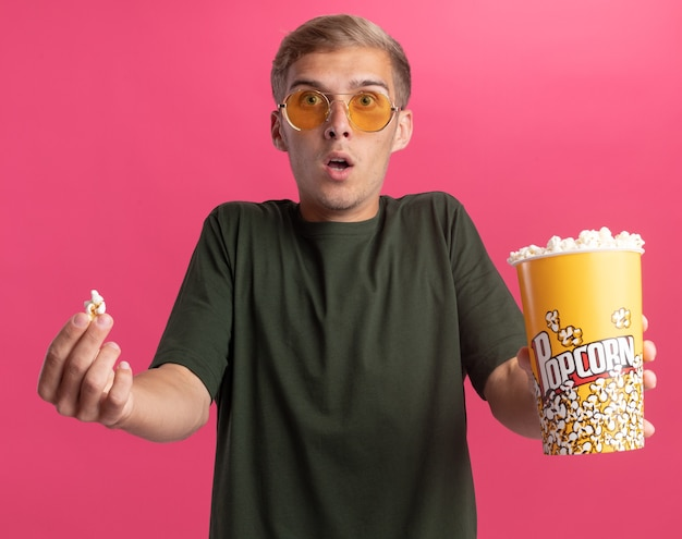Giovane ragazzo bello sorpreso che indossa la camicia verde e gli occhiali che pongono fuori secchio di popcorn con pace di popcorn alla macchina fotografica isolata sulla parete rosa