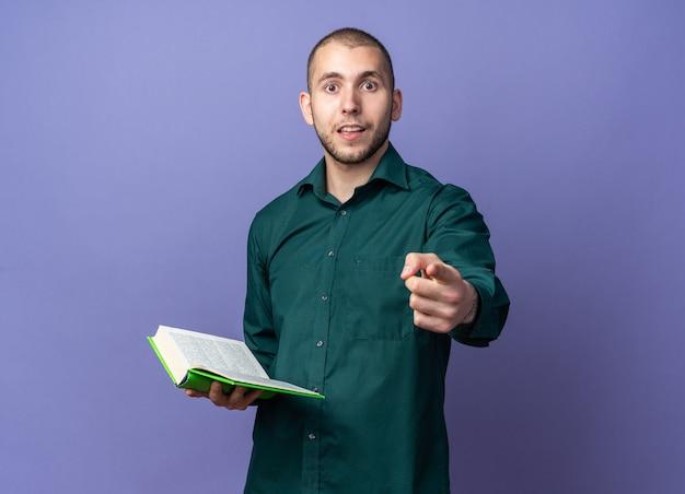 Sorpreso giovane bel ragazzo che indossa una camicia verde che tiene i punti del libro davanti